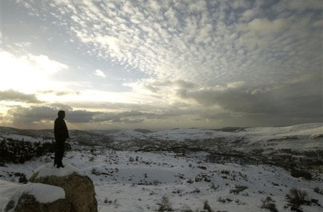 A Lebanese forest ranger observes the sunset from the cedar trees reserve of Baruk in the Shouf mountains, southeast of Beirut, following a snow storm and cold wave which hit the east Mediterranean country after several months of drought.