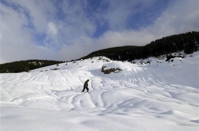 A Lebanese man walks on a snow-covered peak at the cedar trees reserve of Baruk southeast in the Shouf mountains, southeast of Beirut.