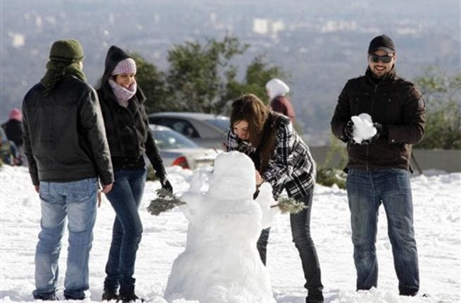 Syrians play with snow in Damascus as the Syrian capital was lashed by a snowstorm which disrupted traffic but brought some relief from a drought which has gripped the country for the past four years.