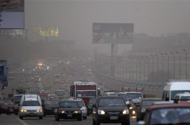 Cars drive amid fog covering Cairo. A sandstorm, strong winds and lashing rains swept across Egypt, closing several ports and disrupting traffic in the Suez Canal while at least three people died in a factory collapse in the Mediterranean city of Alexandria, officials said.