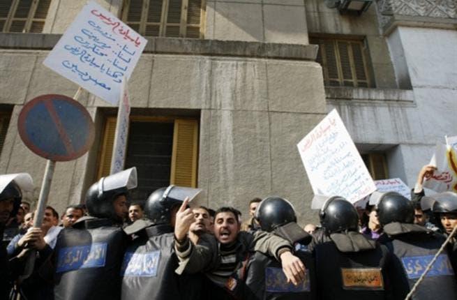 Arabic writing on placard (L) reads: