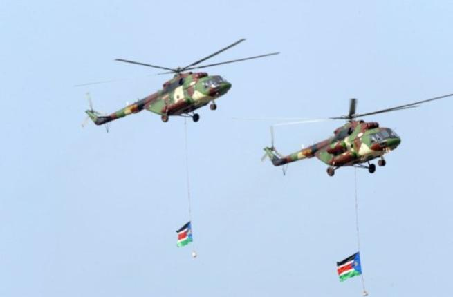 Southern Sudanese military helicopters fly an overpass carrying two Southern Sudan flags during a ceremony in the capital Juba on July 9, 2011 to celebrate South Sudan's independence from Sudan.