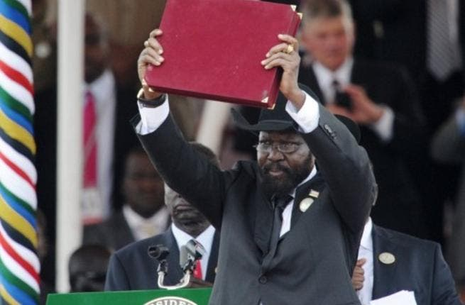 The President of Southern Sudan Salva Kiir waves the newly signed constitution of his country for the crowd to see.