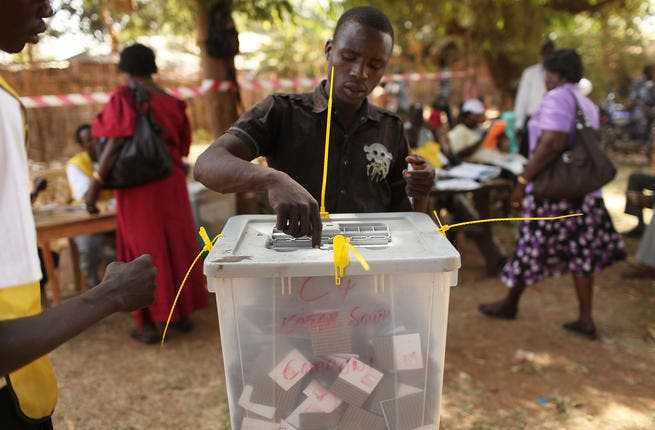 A man places his vote in a plastic box at a polling station.