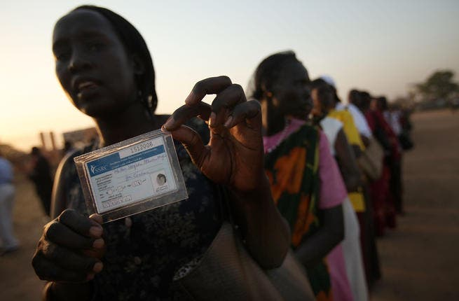 A woman displays her voting card while in line to vote.