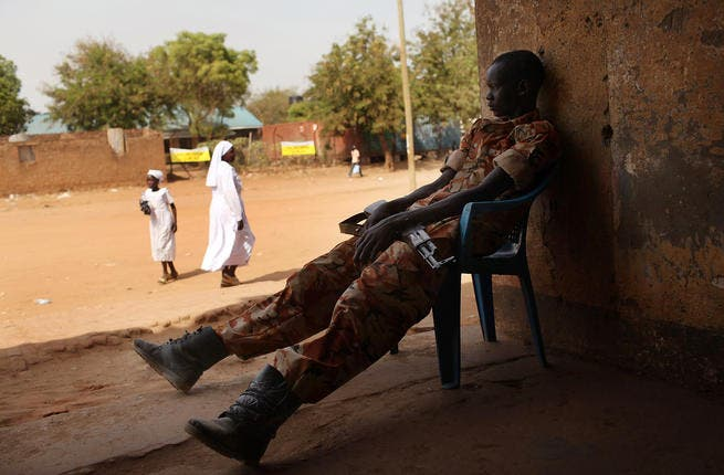 A south Sudanese police officer guards a polling station.