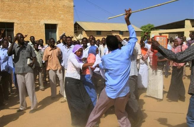 A Sudanese man holding a cane scuffles with university students after clashes erupted during a protest  against the visit of Darfur mediators from Qatar and the UN outside the University of Zalingei in western  Darfur.