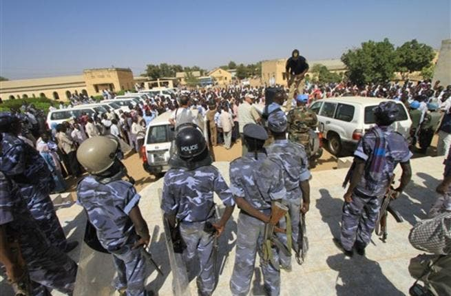 Sudanese policemen stand guard as university students gather during a protest against the visit of Darfur mediators from Qatar and the UN outside the University of Zalingei in western Darfur.