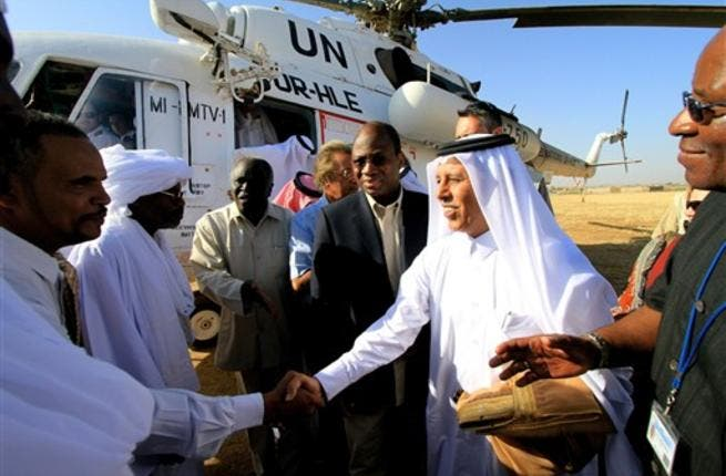 Djibril Bassole, chief negotiator for the UN and the African Union, and Qatari Minister of State for Foreign Affairs Ahmed bin Abdullah al-Mahmud are greeted by local Sudanese.