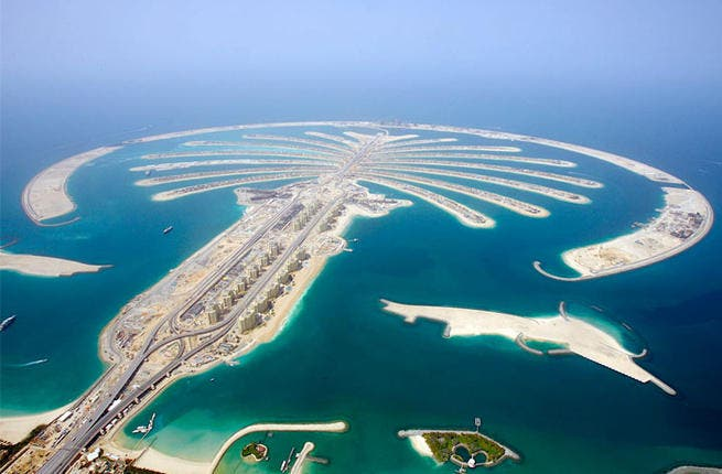 "Fake it! Dip your speculating palms into the world's largest artificial archipelago: Palm Jumeirah, one of Dubai's 3 Palm Islands, has a housing project going swimmingly in this fancy ground constellation (best enjoyed from a helicopter view). In September Palm Jumeirah Villas sold 98% of the 702 ""unique business model"" units for $654 million."