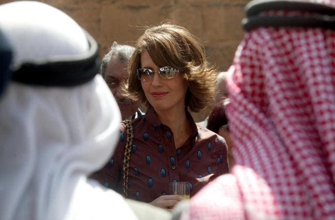 The British banker looks out at her subjects: Asma Al Assad, philanthropist to Syria's children, looks like she might smile as she sips a glass of juice at this function with men dressed like they belong on the set of Lawrence of Arabia. Asma's own style sense, seen in this photo, is  a little bit more au fait.