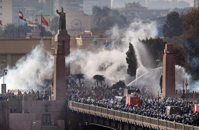 Riot police force protesters back across the Kasr Al Nile Bridge as they attempt to get into Tahrir Square in downtown Cairo, Egypt.