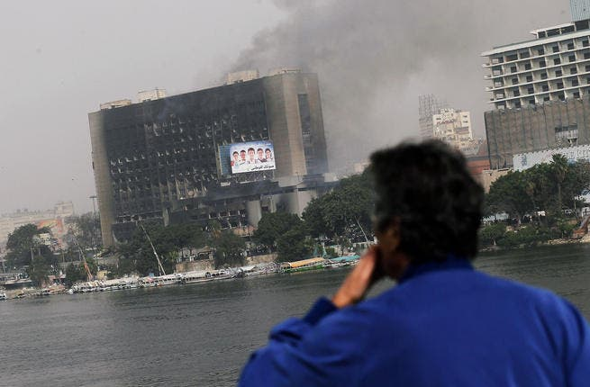 An Egyptian man looks out onto a burning government building from a bridge in central.
