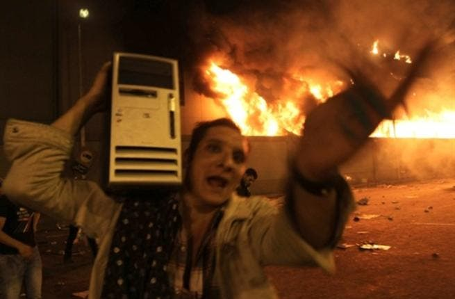 An Egyptian man loots a computer from the burning headquarters of the of the ruling National Democratic party.