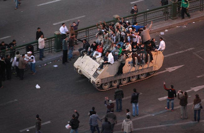 Protesters ride an armored personnel carrier towards the Nile.