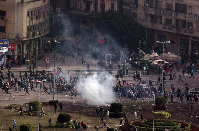 Protesters flee a volley tear gas in Tarhir Square.