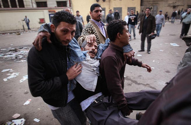 Protesters carry an injured man during clashes with riot police near Tahrir Square.