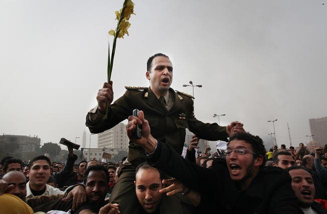 Protesters carry an army captain on their shoulders after he tore up a poster of Egyptian President Hosni Mubarak.