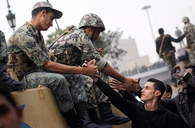 Marchers shake hands with Egyptian Army soldiers on tanks during a demonstration.