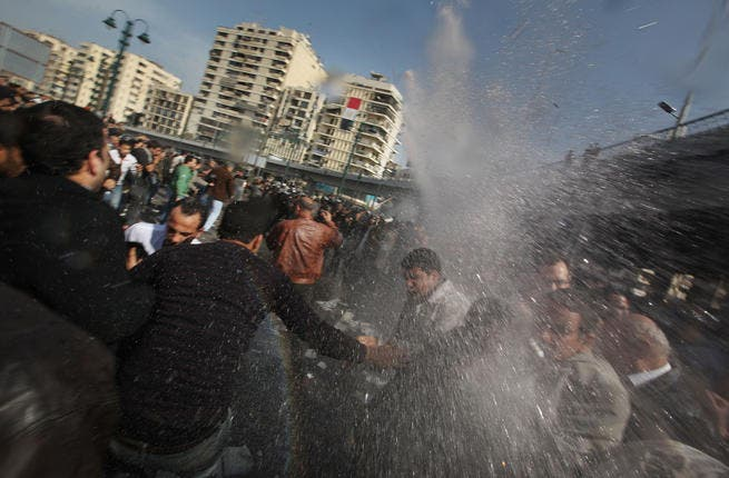 Protesters are hit by a water cannon in front of The l-Istiqama Mosque, as they're watched by riot police in Giza.