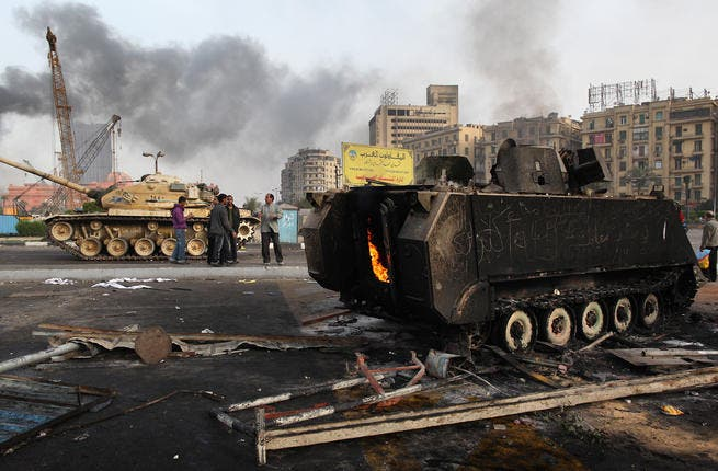 An army tank stands near the remains of a burnt out armored personnel carrier in Tahrir Square.