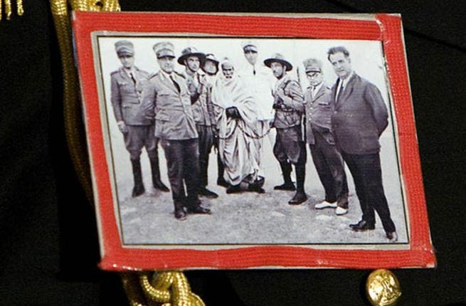 Brazenly sports this self-fashioned badge of Omar Mukhtar national hero who died resisting Italian rule of Libya ( on a visit to Berlusconi's Italy no less)