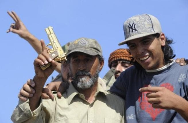 Jeering mobs have their moment. One man struck the former dictator with his shoe -- a grave insult in the Arab world. Shown  here wielding what they claim to be the gold-plated gun of ousted Gaddafi at the site where the latter was captured in the coastal Libyan city of Sirte. His golden gun hardly served the tattered man in his final moments.