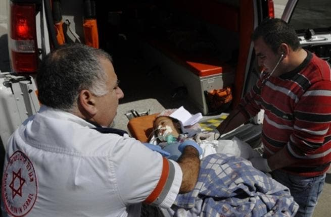 Israeli and Palestinian paramedics treat a wounded Palestinian boy being transfered for medical treatment to an Israeli hospital after he was injured in an Israeli army attack on the Palestinian Gaza Strip.