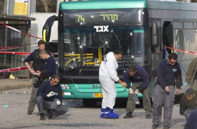Israeli paramedics inspect the scene of an explosion next to a bus near Jerusalem's central bus station which left thirty people hurt
