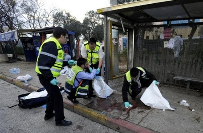 Israeli volunteers from the Zaka organization clean the blood stains and collect human remains at the scene of an explosion near Jerusalem's central bus station.