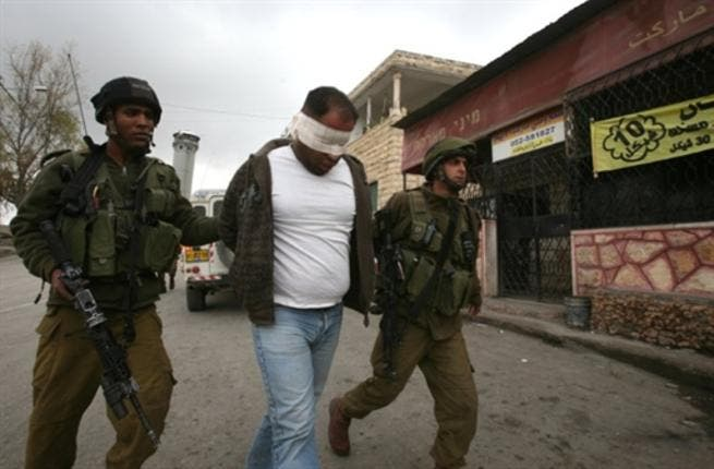 Israeli soldiers lead away a blind folded Palestinian man during a military operation at the entrance of the village of Beit Omar village in the Israeli occupied West Bank.