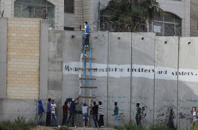 Al-Ram - Palestinians climb over the Israeli separation barrier in the West Bank village of Al-Ram, heading to the al-Aqsa mosque to pray on July 19. (AFP / Abbas Momani)