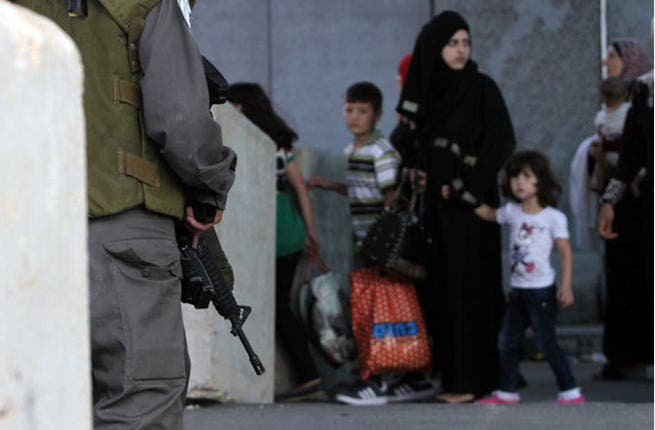 Qalandia's children under the barrel of a gun -  Frightened-looking children gaze at soldiers' guns at the checkpoint as their mother negotiates their way to the other side. (AFP / Abbas Momani)