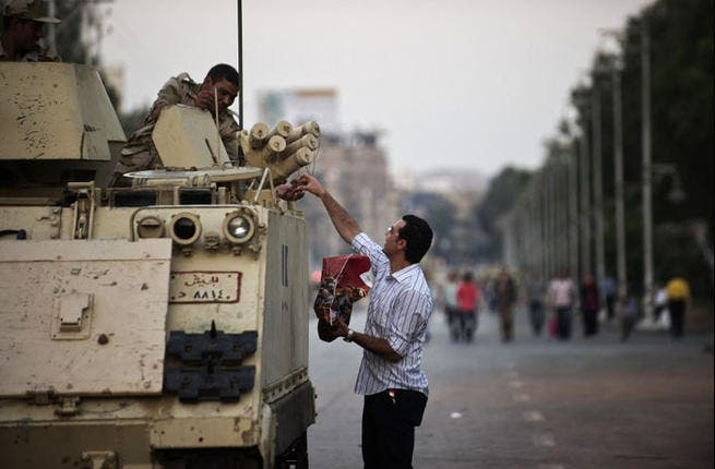 A date with a soldier? Egypt's army needs all the fuel they can get to keep the country stable right now, and the military guard cannot let down their guard even at Iftar time. AFP/GIANLUIGI GUERCIA