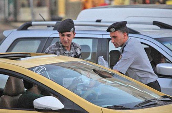 While Amman's yellow cabbies shuttle the punters, the police see fit to serve them their first bite of the fasting day.  (Image courtesy of Ammon news)