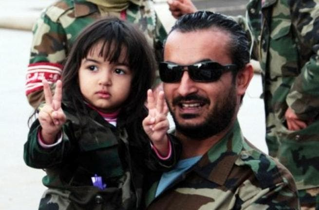 A promising future awaits the new Libyan generation: A man celebrates with child the capture of once heir apparent of late father Colonel Gaddafi. Libyan leaders promise that his second son will be tried in the International Criminal Court (ICC), and held to account for charges against him, possibly answering to the crimes of his untried father.