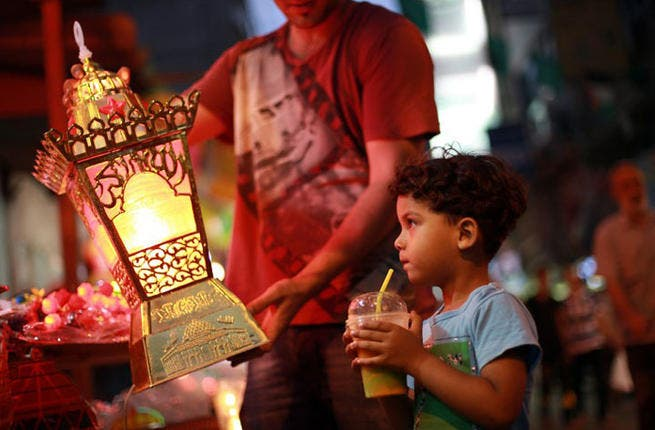 A ray of hope: A Palestinian child admires a traditional Ramadan lantern in a street market in Gaza City. July 6, 2013 (AFP PHOTO/MOHAMMED ABED)