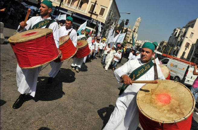 Tripoli, Lebanon: The drums of Ramadan could double as the drums of war if today's explosion is any indicator. Sufi men parade, playing religious music, in traditional attire during a march prior to the start of Ramadan in the streets of the northern Lebanese city of Tripoli. July, 8, 2013. (AFP PHOTO / IBRAHIM CHALHOUB)
