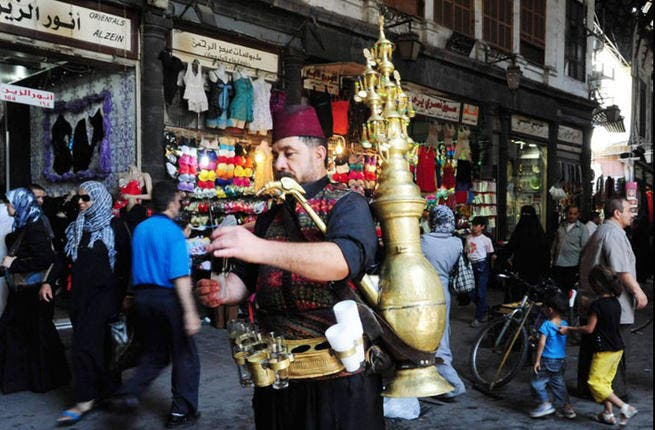 Syria sets its stalls out to get through another Ramadan in (one) peace: A man pours a traditional drink in central Damascus on July 9, 2013 as Syrians shop in preparation for the Muslim holy fasting month of Ramadan. (AFP PHOTO / STR)