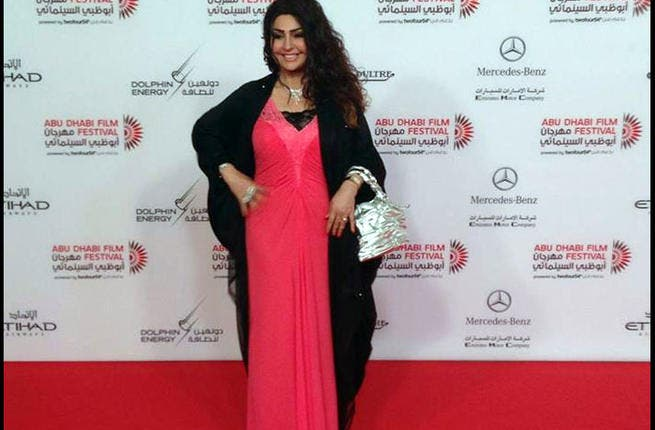 """Here's what we think of Huda Al Khatib's """"dress"""": It belongs to her nightstand, not her evening wardrobe! The clue that this get-up is more nightdress or negligee than evening gown is in the exposed black slip, the tacky pink material and the messy bed-hair! Do us a favor Huda, lose that silver lunchbox you're carrying!"""