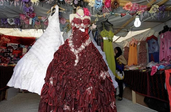 A woman looks at dresses in a covered stall in the northern Jordanian Zaatari refugee camp, now home to 160,000 Syrians (AFP)