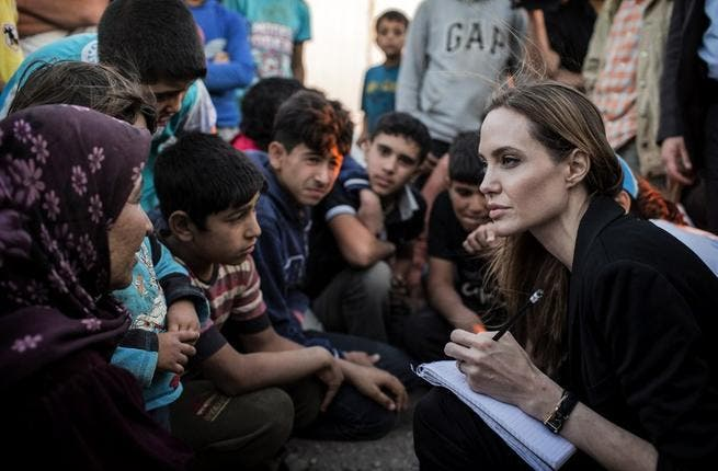 US actress Angelina Jolie listening to Syrian refugees in a Jordanian military camp based the the Jordan-Syria border (UNHCR / AFP)