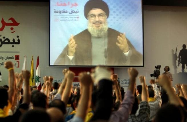 Supporters of Hassan Nasrallah (portrait), the head of Lebanon's militant Shiite Muslim movement Hezbollah raise their fists as they watch him giving a televised address in Beirut last week (AFP)