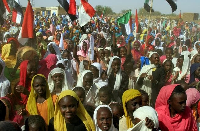 Sudanese women wave their national flag as they wait for the arrival of special envoys in the Shangil Tobaya area for displaced people in North Darfur state (AFP)