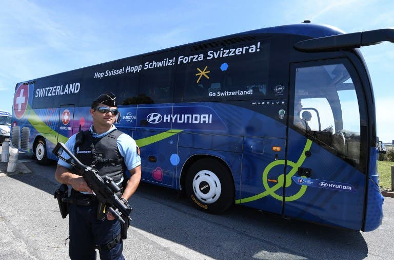 A policeman stands guard as Switzerland's national football team leaves Montpellier's airport by bus, on June 6, 2016, four days ahead of the start of the Euro 2016 European football championships. PASCAL GUYOT / AFP