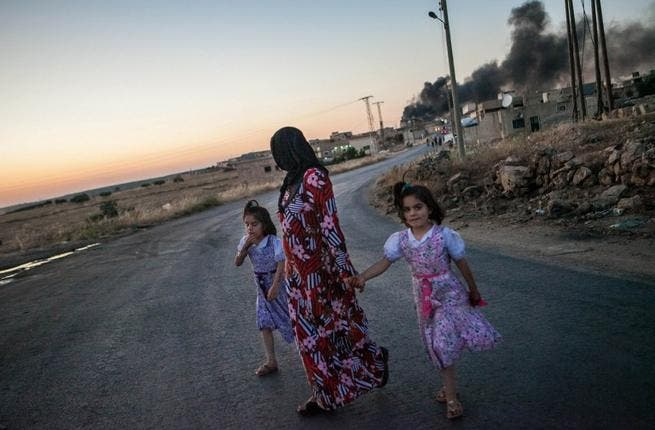 A woman walks with two children, looks back at smoke billowing in Idlib province (AFP)