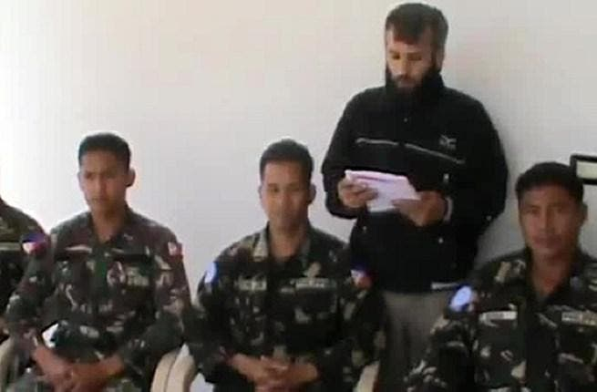 An image grab taken from a video uploaded on YouTube on May 08, 2013 reportedly shows a man reading a statement at an undisclosed location in Syria, behind four abducted Filipino UN peacekeepers. (AFP/ YouTube)