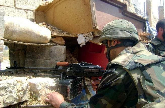 A handout picture released by the Syrian Arab News Agency (SANA) on May 20, 2013, allegedly shows a Syrian soldier scanning the area for hostiles in the the town of Qusayr in Homs province (SANA / AFP)