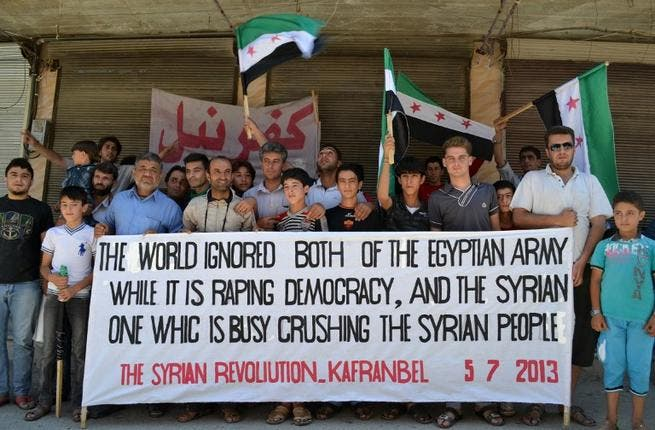 Syrian demonstrators posing with a banner referring to the situation in both Syria and Egypt during an anti-regime protest in Kfar Nubul in the northwestern province of Idlib (Shaam news network / AFP)