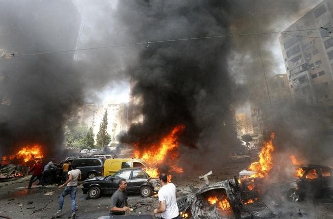 Civilians gather at the of an explosion in Beirut's southern suburb neighbourhood of Bir al-Abed on July 9 (AFP)